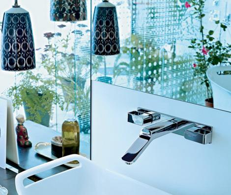 Baterie łazienkowo naścienne w nowoczesnym stylunamontowana nad nietypową umywalką bezpośrednio pod lustrem