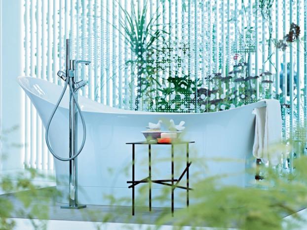 baterie łazienkowe sztorcowe  wolnostojące koło wanny wolnostojącej z wyglądzie bali na tle zieleni