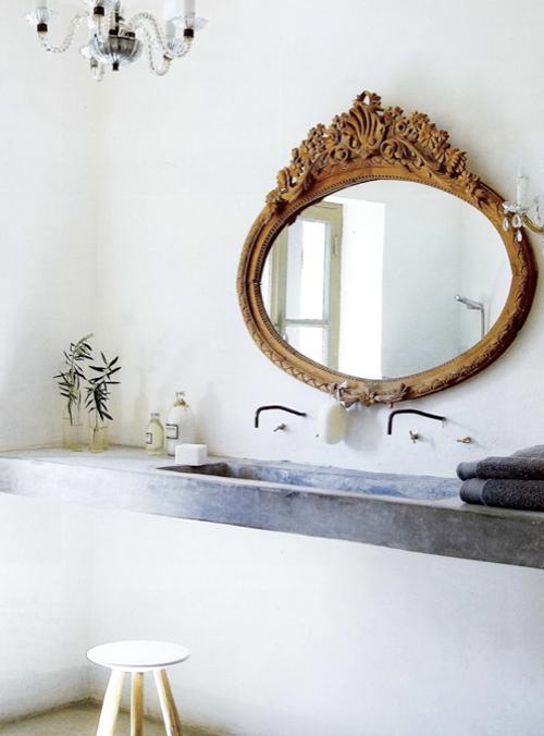 Modernistyczna umywalka stanowiąca również betonowy blat w kontrastowym zestawieniu z starodawnym złotym lustrem i starymi bateriami