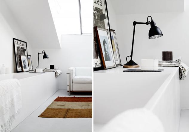 łazienka w stylu skandynawskim z czarnymi dodatkami na przykład w postaci lampki czy ram zdjęć stojących na wanny