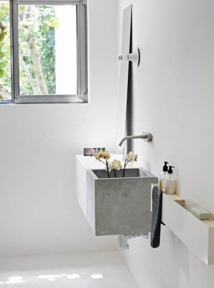 kwadratowa umywalka z kamienia w kolorze szarym połączona z białymi meblami