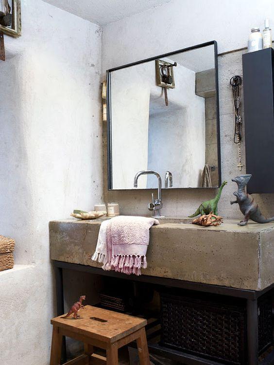 prosta umywalka z kamienia w surowej łazience z poustawianymi figurkami dinozaurów