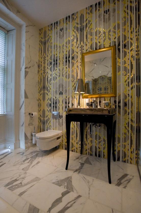 złota mozaika łazienkowa uzupełnia marmurowe wnętrze łazienki z lustrem w złotej ramie