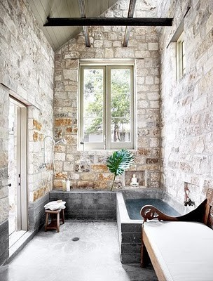 łazienka rustykalna z cegłami na ścianach , kamienną podłogą i rustykalnymi dodatkami