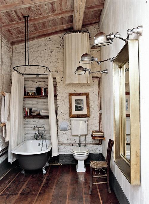 """łazienka rustykalna w w typowo """"wiejskim"""" stylu z kamieniami z ścianach, belkach na suficie i deskach na podłodze. Wolno stojąca żeliwna wanna i piękne duże w złotej ramie lustro"""