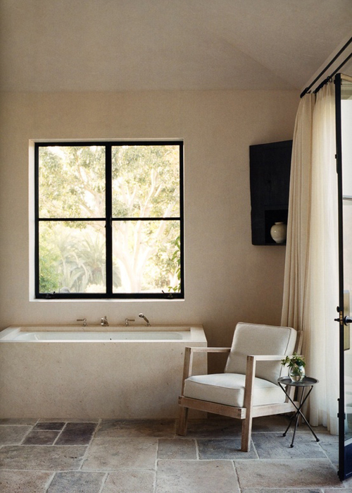 łazienka rustykalna ze skosami w kamienną podłogą, zabudowaną wanną, duże okno i wyjście na taras dodaje przytulny klimat pokoju kąpielowego w barwach kremu
