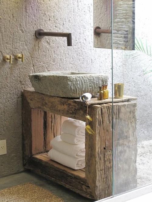 łazienka rustykalna ze ścianami z surowego kamienia i kamienną umywalką postawioną na stoliku ze starego drewna, dodatki w kolorze złota