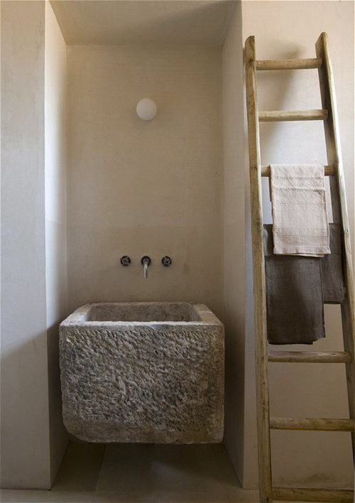 minimalistyczna łazienka rustykalna z umywalka wykutą z surowego szarego kamienia, z drabiną zastosowana jako podajnik do ręczników