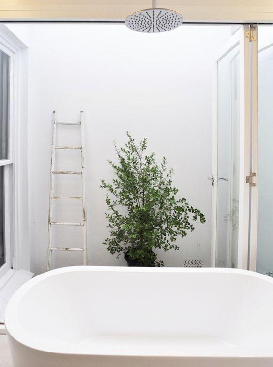 biała wanna wolnostojąca z deszczownicą zamontowaną bezpośrednio nad nią w białej łazience