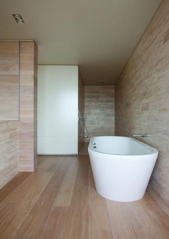 biała wanna wolnostojąca w łazience gdzie podłoga wyłożona została panelami podłogowymi