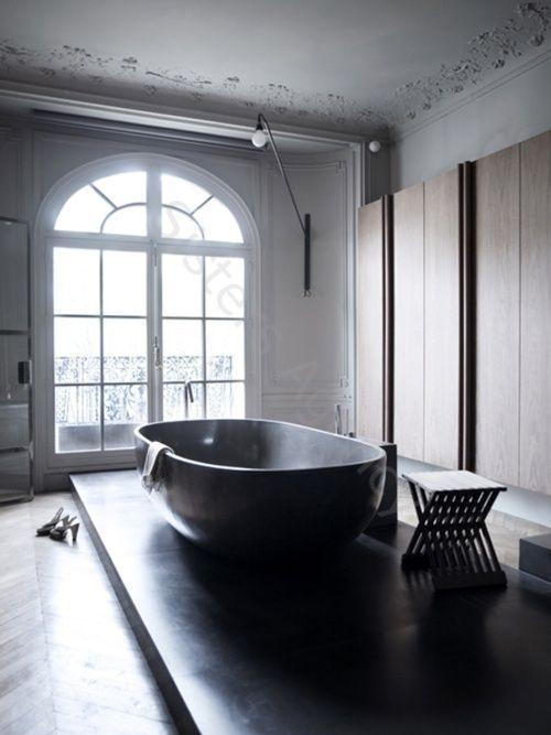 Wielka wanna wolnostojaca z konglomeratu na takim samym podeście w pomieszczenie z wysokim oknem zakończonym łukiem, ze stylizowanym sufitem