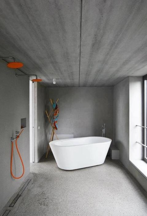 betonowa łazienka z dużym oknem, wolnostojącą białą wanną i pomarańczowymi wylewkami prysznicowymi