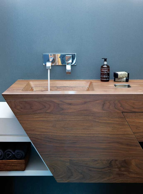 drewniana podwieszana umywalka na tle niebieskiej ściany z podtynkową srebrną baterią