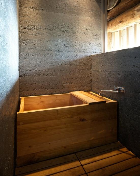 drewno w łazience w postaci małej wanny w surowym, szarym pomieszczeniu