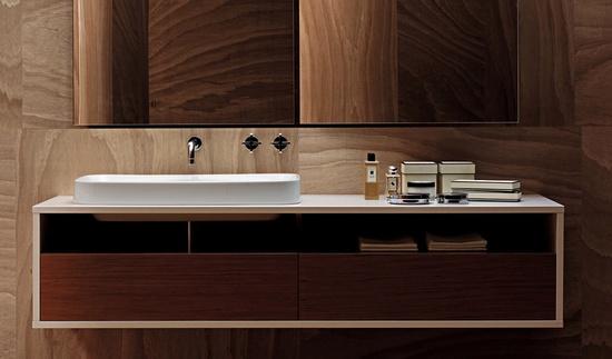 drewno w łazience zastosowane w postaci kwadratowych paneli pokrywa cała powierzchnię ścian i podłogi, całość wykończone podłużnym lustrem nadającym głebi