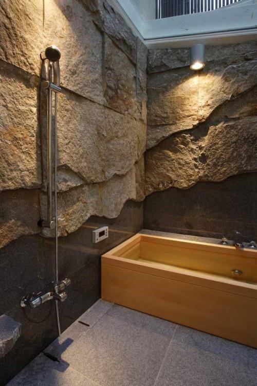 prostokatna drewniana wanna w oryginalnej łazience gdzie sciany wygladaja jak wnetrze jaskini