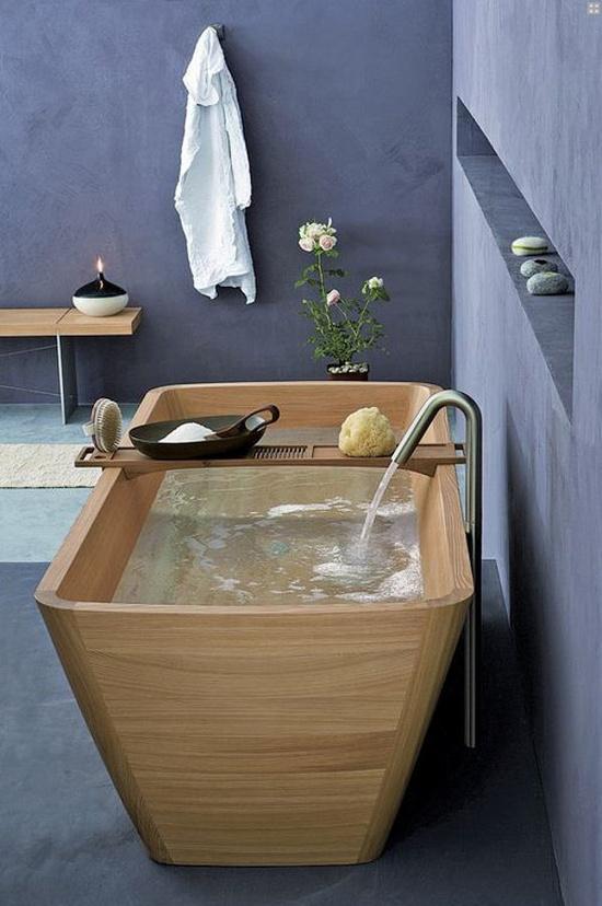 drewniana wanna z wlewająca się wodą we wrzosowej łazience