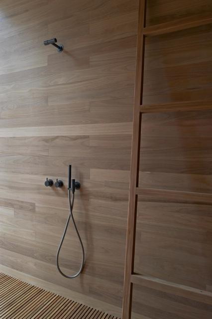 drewno w łazience wykorzystane na całej powierzchni ściany pod prysznicem z czarną podtynkową baterią i oryginalną wylepką