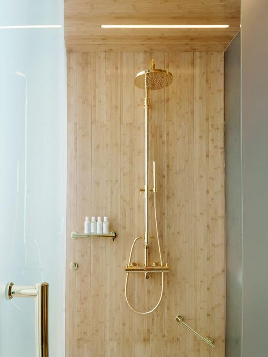 drewno w łazience wykorzystane do wykończenia wnątrza prysznica ze złotą barerią i wylewką wylewką
