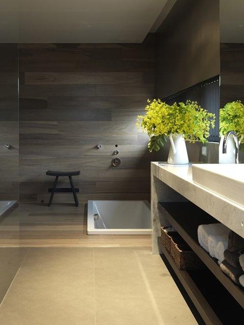 drewno w łazience w postaci ciemnobrązowych poziomych paneli i gres kolorze kawy z mlekiem nadają pomieszczeniu wschodniego smaku. Dodatkowo wpuszczona w podłogę wanna powiększa go optycznie