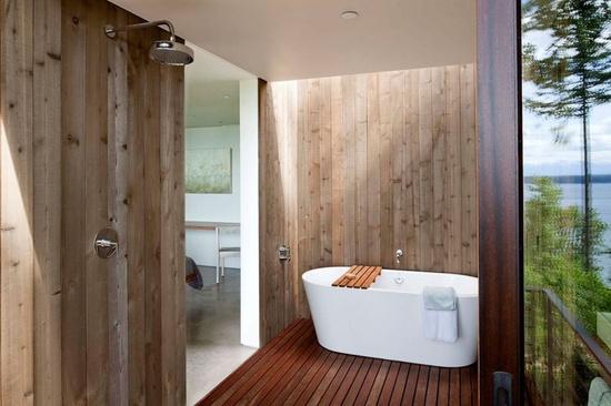 drewno w łazience wykorzystane jako wykończenie prysznica, pokrywa boczną ścianę przy białej nowoczesnej wannie jak również na podłodze