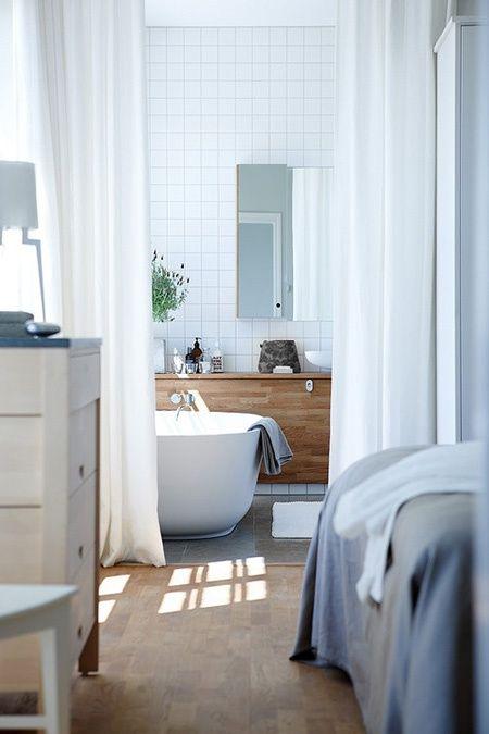 wanna wolnostojąca w małej łazience połączonej z sypialnią oddzieloną białymi zasłonami