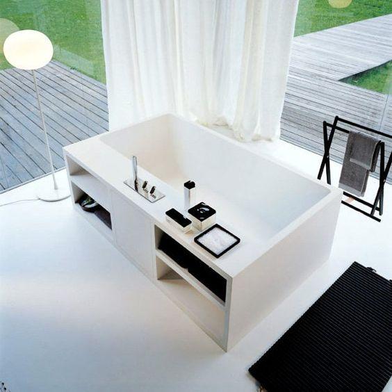 wanna wolnostojąca z półkami na bokach ustawiona w przeszklonym pomieszczeniu w białej aranżacji