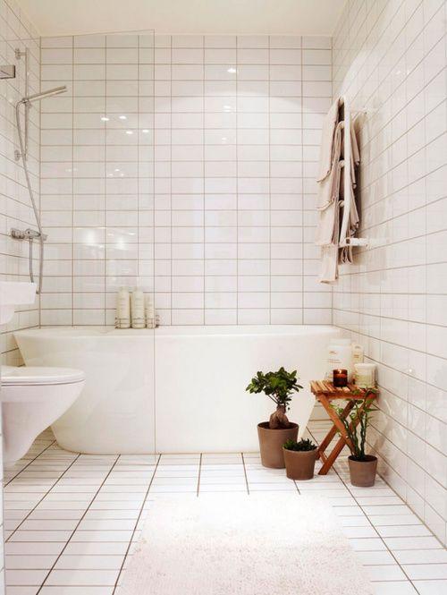 wanna wolnostojąca w białej łazience z możliwością prysznica