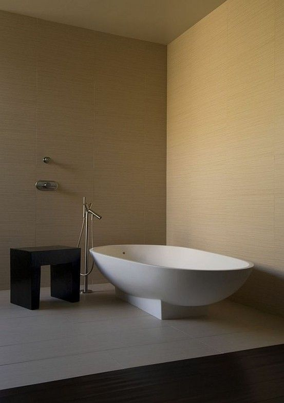 wanna wolnostojąca o nietypowym kształcie w minimalistycznej łazience ze srebrną wylewką