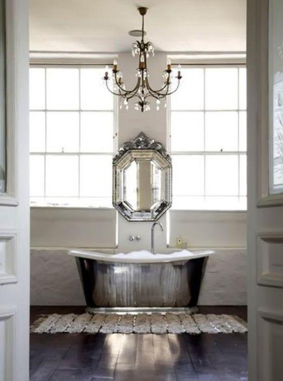 srebrna wanna retro w pałacowym pomieszczeniu z ciemna podłogą i kryształowym lustrem
