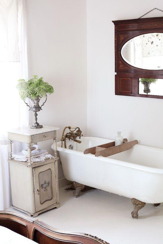 wanna retro z drewnianą półką na kosmetyki w otoczeniu mebli łazienkowych w stylu rustykalnym