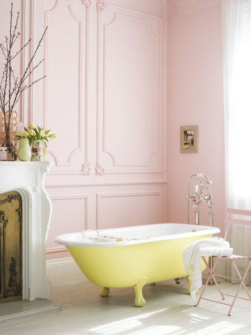 żółta wanna retro przy kominku w różowo-pudrowym pokoju