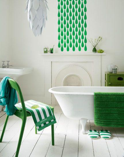 stylizowana wanna retro, umywalka, podłoga i kominek uzupełniona nowoczesnymi detalami i dodatkami w kolorze świeżej zieleni