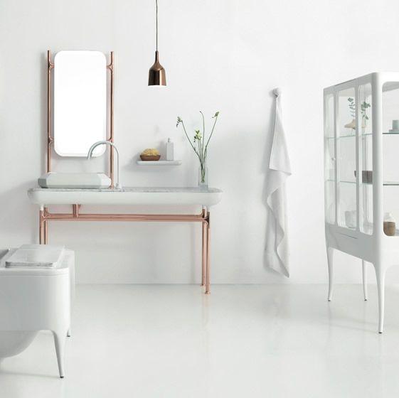 meble łazienkowe wykończone miedzianymi rurkami z lampą wiszącą w kolorze miedzianym, całość w białej minimalistycznej łazience z witryną i wanną w modernistycznym stylu