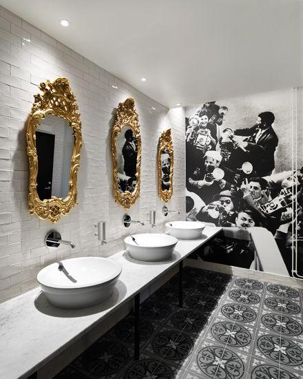 oświetlenie łazienkowe w formie wpuszczanych opraw halogenowych w suficie nad nowoczesnymi okrągłymi umywalkami z lustrami w złotych ramach z florystycznym wzorem