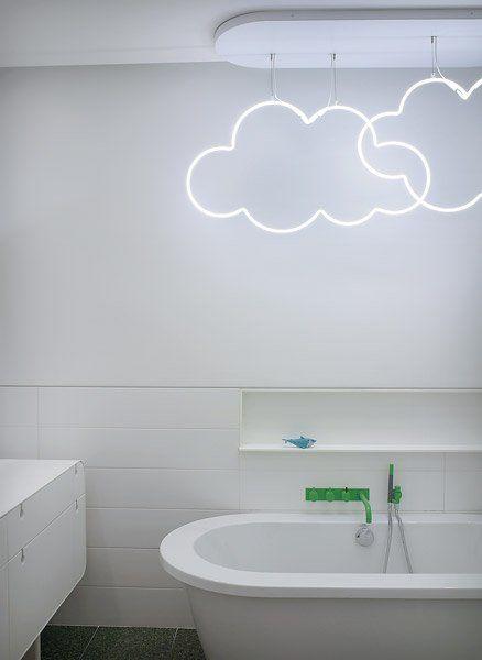 oświetlenie łazienkowe w postaci neonowych chmurek bezpośrednio wiszące nad wanną.