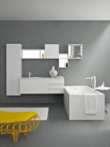 meble łazienkowe, kompozycja z białych szafek ściennych na szarej ścianie , biała prosta wanna z białą baterią i żółte siedzisko