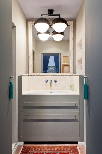 oświetlenie łazienkowe w postaci dużej podwójnej lampy sufitowej w czarnej oprawie nad umywalką w głębi