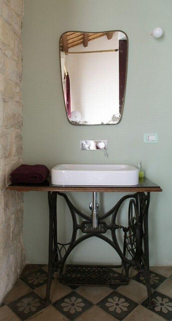 stare elementy sprzętów mieszkania użyte jako meble łazienkowe, w tym przypadku to podstawa starodawnej maszyny do szycia jako stolik pod umywalkę w łazience ze skosami na poddaszu