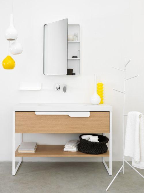 Białe, nowoczesne meble łazienkowe z drewnianymi frontami w minimalnej jasnej łazience i żółtymi dodatkami w postaci wazonów i elementów oświetlenia