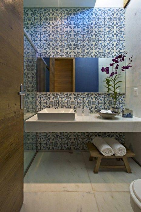 meble łazienkowe zastąpione marmurowym blatem na którym jest umywalka, całość w pięknych wzorzystych płytkach pasujących do koloru ścian na przeciwko lustrzanej szafki