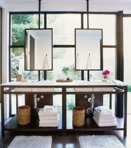 meble łazienkowe otwarte składające się ze stelaża w wpuszczonymi umywalkami nad którymi wiszą proste lustra, całość na tle przestronnego okna