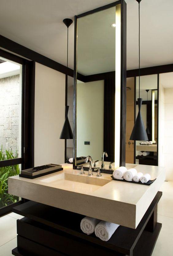 oświetlenie łazienkowe Toma Dixona - czarne lampy po obu stronach lustra