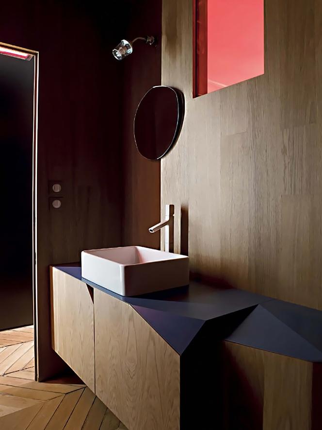 meble łazienkowe z frontami w kolorystyce paneli naściennych w łazience, szafki z nietypowym pościnanymi brzegami, jakby złamanymi