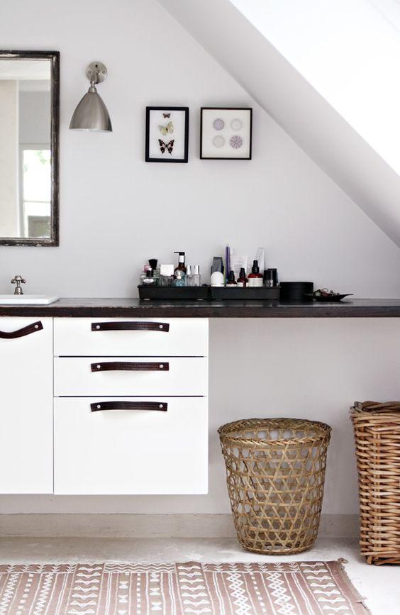 dekoracje do łazienki w formie uporządkowanych kosmetykach na czarnych tacach na czarnym blacie z koszami wiklinowymi pod spodem