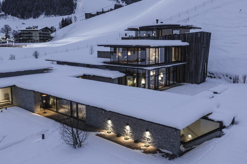 Hotel Wiesergut projektu Gogl Architekten nocą w zimowym krajobrazie