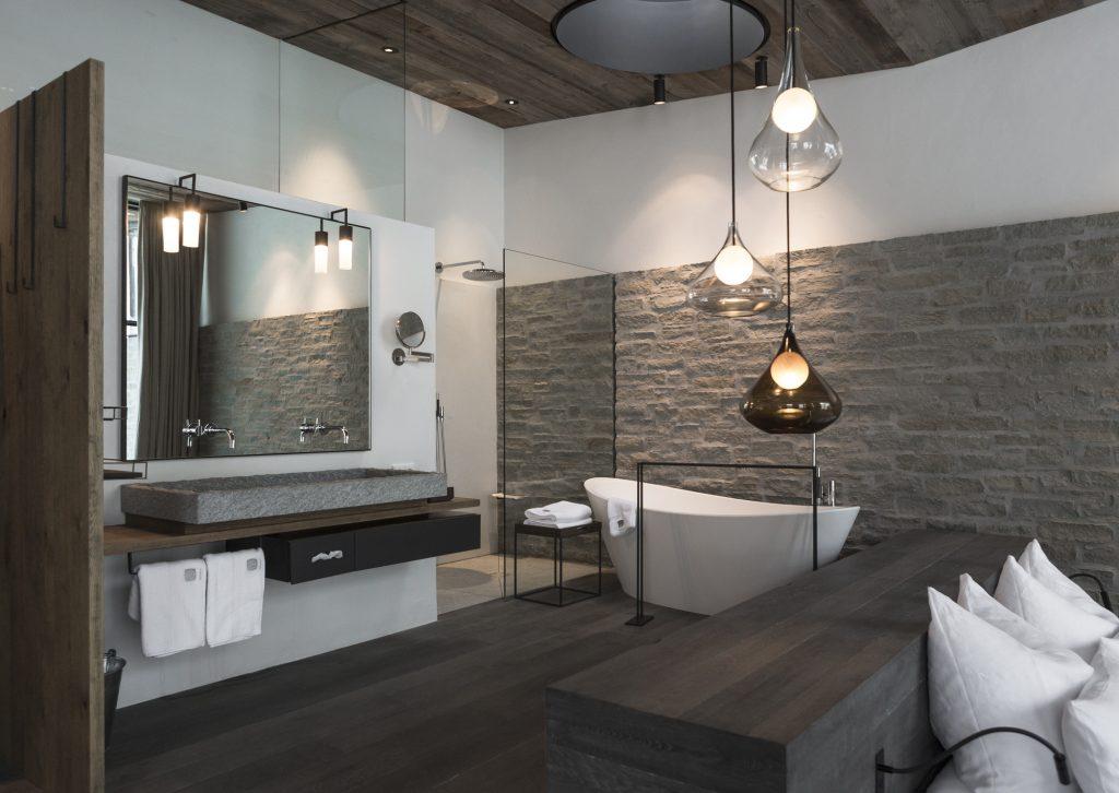 aranżacja łazienki w kamieniu i ciemnym drewnie z nowoczesną białą wanną