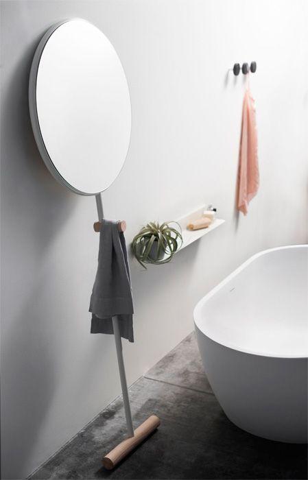 dekoracje do łazienki w formie lustra na nóżce, minimalistycznych wieszaczków i łososiowego ręcznika
