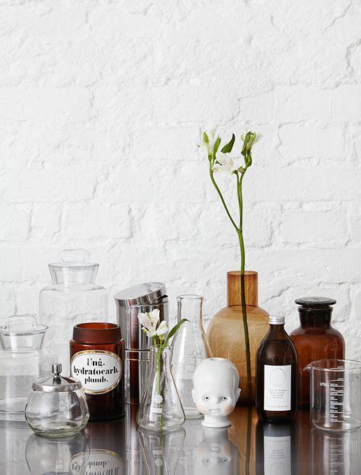 dekoracje do łazienki w stylu aptekarskim, butelki, szklane pojemniczki, zlewki na tle bielonej ceglanej ściany