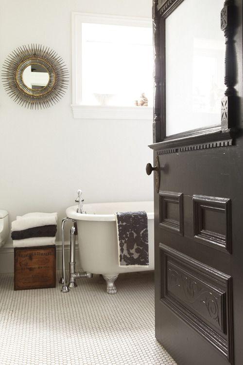 Dekoracje do łazienki w formie białych i czarnych ręczników, skrzyni i oryginalnego lustra nadają charakteru